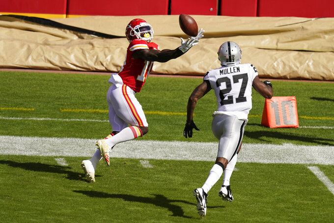 Kansas City Chiefs wide receiver Tyreek Hill, left, catches a pass ahead of Las Vegas Raiders cornerback Trayvon Mullen (27) during the first half of an NFL football game, Sunday, Oct. 11, 2020, in Kansas City. (AP Photo/Charlie Riedel)