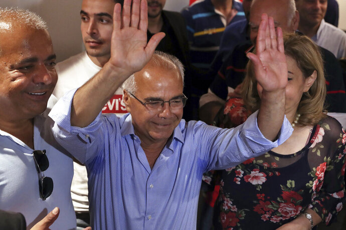 Mohammed Saleh who was detained in Greece last week, raises his hands upon his arrival at the Rafik Hariri International Airport in Beirut, Lebanon, Wednesday, Sept. 25, 2019. Saleh, a Lebanese journalist was mistakenly detained in Greece on suspicion of involvement in a 1985 TWA hijacking has arrived home in Lebanon. (AP Photo/Bilal Hussein)