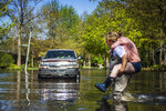 Ryan Stadelmaier, 16, gives a piggyback ride to his sister Rachel Stadelmaier, 27, as they cross Walden Woods Drive while helping residents tend to their flooded homes, Wednesday, May 20, 2020, in Midland, Mich. (Katy Kildee/Midland Daily News via AP)