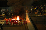 Protesters set fire to a barricade to prevent riot police officers from advancing in Hong Kong on Sunday, July 21, 2019. Hong Kong police launched tear gas at protesters Sunday after a massive pro-democracy march continued late into the evening. The action was the latest confrontation between police and demonstrators who have taken to the streets to protest an extradition bill and call for electoral reforms in the Chinese territory. (AP Photo/Bobby Yip)