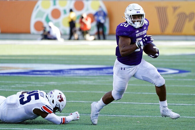 Northwestern running back Cam Porter, right, runs for yardage past Auburn linebacker Colby Wooden (25) during the second half of the Citrus Bowl NCAA college football game, Friday, Jan. 1, 2021, in Orlando, Fla. Northwestern beat Auburn 35-19. (AP Photo/John Raoux)