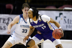 FILE - Western Carolina forward Xavier Cork (13) drives the ball against Citadel forward Hayden Brown (33) in the first half of the first round NCAA men's college basketball championship game for the Southern Conference tournament in Asheville, N.C., in this Friday, March 5, 2021, file photo. TCU has eight transfers this season, including Xavier Cork, who shot 64% at Western Carolina in the Southern Conference. (AP Photo/Kathy Kmonicek, File)