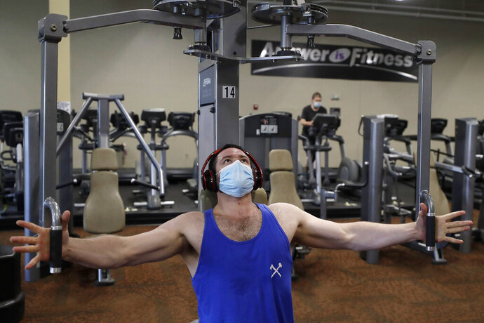 A customer at Answer is Fitness gym, who asked that his name not be used, works out on a piece of exercise equipment, Monday, July 6, 2020, at the gym, in Canton, Mass. Casinos, gyms, movie theaters, and museums are among the businesses allowed to reopen in the state on Monday, under the third phase of Massachusetts Gov. Charlie Baker's coronavirus economic recovery plan. The rules don't apply to Boston, which is to move into phase three on July 13. (AP Photo/Steven Senne)