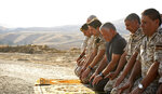 Jordan's King Abdullah II, third right, prays during a tour of the Baqura enclave formerly leased by Israel, with Crown Prince Hussein, fourth right, and military officers, Monday, Nov. 11, 2019. Jordan's decision not to renew the leases on the Baqura and Ghamr enclaves, known in Hebrew as Naharayim and Tzofar, were a fresh blow to Israel and Jordan's rocky relations 25 years after the two countries signed a peace deal. (Yousef Allan/Jordanian Royal Court via AP)