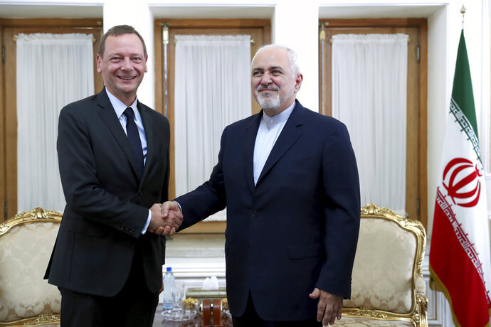 Iranian Foreign Minister Mohammad Javad Zarif, right, shakes hand with French presidential envoy Emmanuel Bonne, as they pose for photos, in Tehran, Iran, Wednesday, July 10, 2019. France sent Bonne to Tehran to urge Iran to return to complying with the terms of the deal