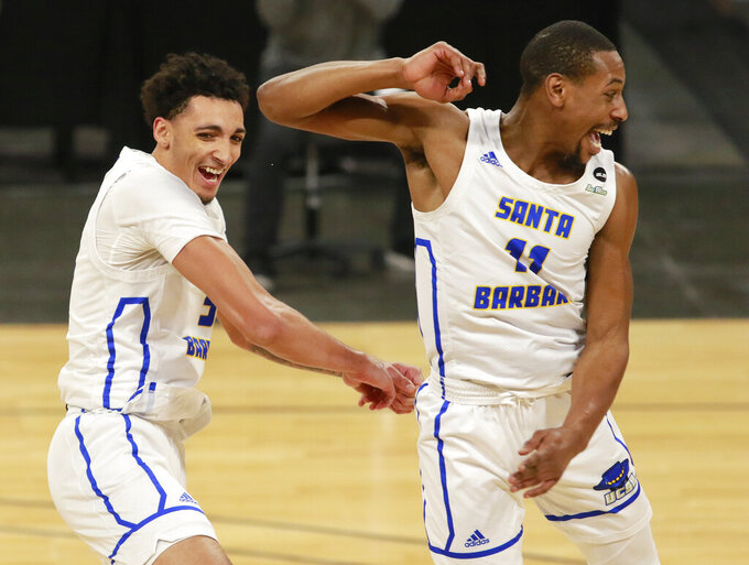 UC Santa Barbara's Miles Norris (5) and Brandon Cyrus (11) celebrate their win over UC Irvine in an NCAA college basketball game for the championship of the Big West Conference men's tournament Saturday, March 13, 2021, in Las Vegas. (AP Photo/Ronda Churchill)