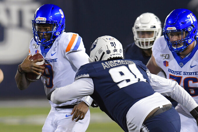 Boise State quarterback Jaylon Henderson (9) runs with the ball as Utah State defensive tackle Devon Anderson (91) moves in during the first half of an NCAA college football game Saturday, Nov. 23, 2019, in Logan, Utah. (AP Photo/Eli Lucero)