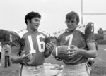FILE - In this July 9, 1971, file photo, College All-Star quarterbacks Jim Plunkett (16) and Dan Pastorini (7) talk at practice in Evanston, Ill., for a charity game against the Baltimore Colts to be played July 30, 1971, in Chicago. In the early days of the NFL, college football was king and playing the game professionally was not necessarily something players aspired to do. By planting its flag in large cities, embracing television exposure and playing a more entertaining style, the NFL surged in popularity in the middle of the 20th century and helped turn college football into a means to an end for many players.  (AP Photo/Charles E. Knoblock)