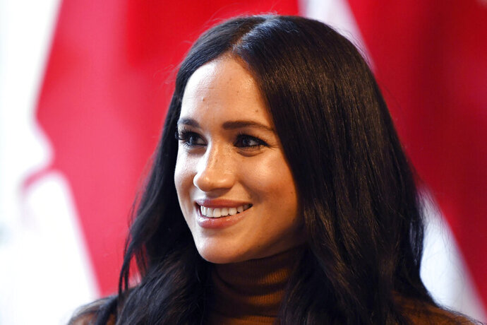 "FILE - In this Tuesday, Jan. 7, 2020 file photo, Meghan, Duchess of Sussex smiles during her visit with Prince Harry to Canada House, in London. The Duchess of Sussex is seeking to delay the start of the trial in her privacy action against a British newspaper over its publication of excerpts from a ""private and confidential″ letter she wrote to her father. The former Meghan Markle, wife of Britain's Prince Harry, made the request ahead of a preliminary hearing on the case scheduled for Thursday, Oct. 29. (Daniel Leal-Olivas/Pool Photo via AP, file)"