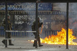 A petrol bomb explodes near a police officer during clashes with anti-government protesters in Santiago, Chile, Monday, Nov. 18, 2019. According to the Medical College of Chile at least 230 people have lost sight after being shot in an eye in the last month while participating in the demonstrations over inequality and better social services. (AP Photo/Esteban Felix)