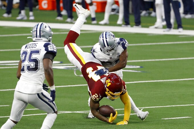 Dallas Cowboys safety Xavier Woods (25) watches as cornerback Rashard Robinson, right, stops Washington Football Team running back Antonio Gibson (24) on a carry in the first half of an NFL football game in Arlington, Texas, Thursday, Nov. 26, 2020. (AP Photo/Roger Steinman)