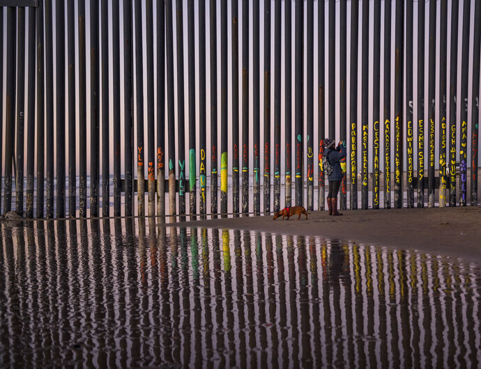 FILE - In this Jan. 3, 2019, file photo, a woman takes a snapshot by the border fence between San Diego, Calif., and Tijuana, as seen from Mexico. The immigration spending Congressional leaders on Thursday, Feb. 14, released details of a compromise on border and immigration enforcement that gives President Donald Trump just a sliver of the money he wanted for his border wall with Mexico. (AP Photo/Daniel Ochoa de Olza, File)