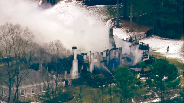 This aerial still image from video provided by WCVB shows firefighters putting out hotspots after a fire damaged a mansion Friday, Dec. 27, 2019, in Concord, Mass.  Firefighters battled the huge blaze at the stately mansion in the Boston suburbs, but struggled to get enough water to it and lost the fight when the roof caved in.  (WCVB-TV via AP)