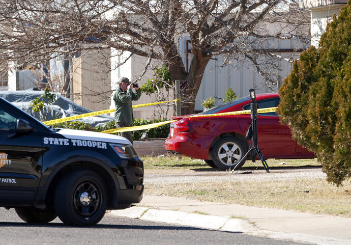 Police investigators take pictures and gather evidence following an officer involved shooting, Thursday, Jan. 23, 2020, in Midland, Texas. (Tim Fischer/Reporter-Telegram via AP)