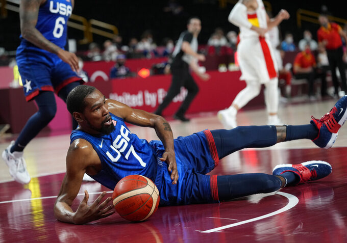 United States' Kevin Durant (7) falls on the court in an attempt to take control of the ball during men's basketball quarterfinal game against Spain at the 2020 Summer Olympics, Tuesday, Aug. 3, 2021, in Saitama, Japan. (AP Photo/Eric Gay)