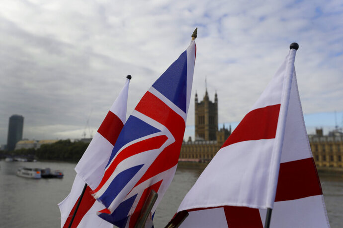 "English flags and a Union flag fly above a souvenir stand opposite Britain's Parliament in London, Friday, Oct. 16, 2020. Britain's foreign minister says there are only narrow differences remaining in trade talks between the U.K. and the European Union. But Dominic Raab insists the bloc must show more ""flexibility"" if it wants to make a deal.  (AP Photo/Kirsty Wigglesworth)"