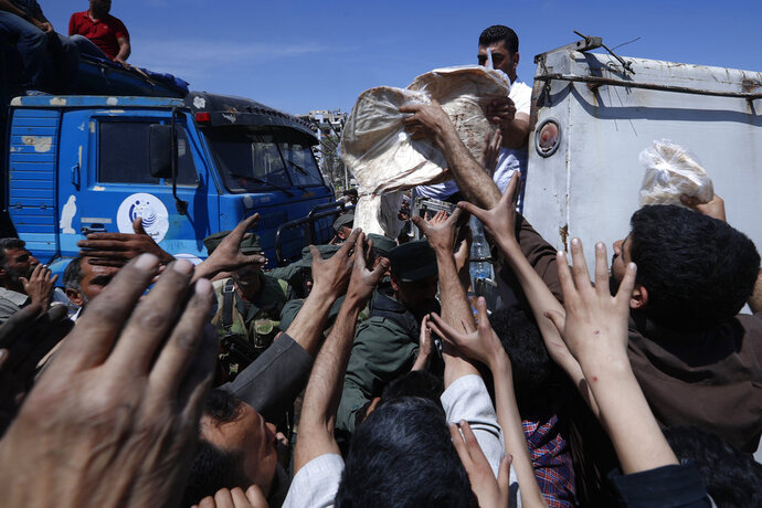 Syrian authorities distribute bread, vegetables and pasta to Douma residents, in the town of Douma, the site of a suspected chemical weapons attack, near Damascus, Syria, Monday, April 16, 2018. Two days after Syrian troops declared Douma, near the capital, Damascus, liberated from rebel fighters and 10 days since a suspected chemical attack, a tour on Monday revealed widespread destruction and traumatized residents who recalled months spent cowering in crowded underground shelters infested with lice, with barely any food or water. (AP Photo/Hassan Ammar)