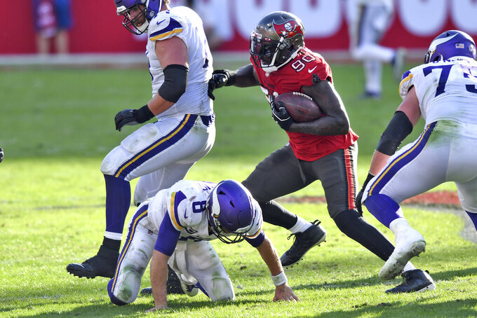 Tampa Bay Buccaneers outside linebacker Jason Pierre-Paul (90) runs with the ball after stripping it away from Minnesota Vikings quarterback Kirk Cousins (8) during the second half of an NFL football game Sunday, Dec. 13, 2020, in Tampa, Fla. (AP Photo/Jason Behnken)