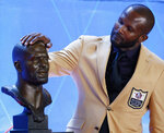 Former NFL player Champ Bailey touches a bust of himself during the induction ceremony at the Pro Football Hall of Fame, Saturday, Aug. 3, 2019, in Canton, Ohio. (AP Photo/Ron Schwane)