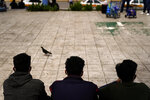 Three men from Honduras sit in a plaza at the border after being returned from the U.S. to Mexico, Thursday, May 13, 2021, in Reynosa, Mexico. The Biden administration has agreed to let up to about 250 people a day in the United States at border crossings with Mexico to seek refuge, part of negotiations to settle a lawsuit over pandemic-related powers that deny migrants a right to apply for asylum, an attorney said Monday. (AP Photo/Gregory Bull)