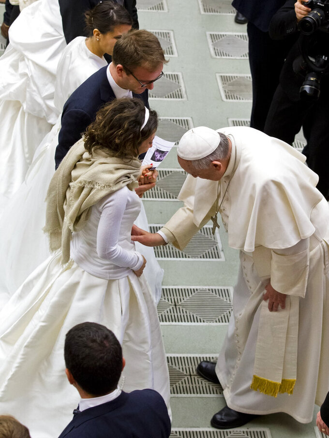 """FILE - In this Wednesday, Feb. 4, 2015 file photo, Pope Francis, right, blesses a newly wed couple during his weekly general audience in the Pope Paul VI hall, at the Vatican. The Vatican has decreed, Monday, March 15, 2021, that the Catholic Church cannot bless same-sex unions since God """"cannot bless sin."""" The Vatican's orthodoxy office, the Congregation for the Doctrine of the Faith, issued a formal response to a question about whether Catholic clergy can bless gay unions. (AP Photo/Andrew Medichini, File)"""