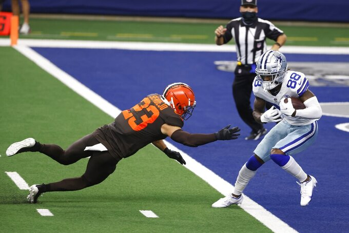Cleveland Browns safety Andrew Sendejo (23) leaps towards Dallas Cowboys wide receiver CeeDee Lamb (88) who catches a touchdown pass in the first half of an NFL football game in Arlington, Texas, Sunday, Oct. 4, 2020. (AP Photo/Ron Jenkins)