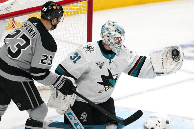 San Jose Sharks goaltender Martin Jones, right, makes a glove save as Los Angeles Kings right wing Dustin Brown stands by during the first period of an NHL hockey game Saturday, April 3, 2021, in Los Angeles. (AP Photo/Mark J. Terrill)