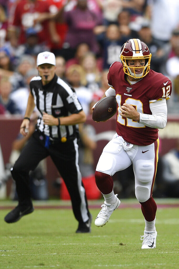 Washington Redskins quarterback Colt McCoy (12) runs for thew sidelines against the New England Patriots during the first half of an NFL football game, Sunday, Oct. 6, 2019, in Washington. (AP Photo/Nick Wass)