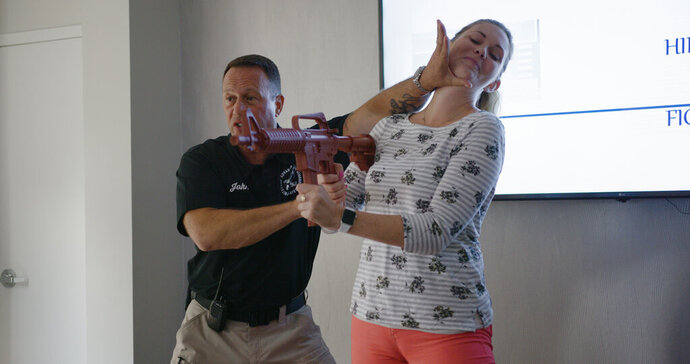 In this July 17, 2019 photo provided by Market Mentors, LLC, John Nettis from PASS, left, demonstrates techniques for fighting with Amanda Moyer, director of account services at Market Mentors at the Market Mentors office in Springfield, Mass. (Justin Bedard/Market Mentors, LLC via AP)