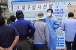 A medical worker guides people as they wait to get coronavirus testing at a makeshift testing site in Seoul, South Korea, Saturday, Sept. 25, 2021. (AP Photo/Ahn Young-joon)
