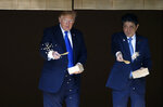 FILE - In this Nov. 6, 2017, file photo, U.S. President Donald Trump, left, and Japanese Prime Minister Shinzo Abe feed carp before their working lunch at Akasaka Palace in Tokyo. Trump's Japan visit starting on Saturday, May 25, 2019, is to focus on personal ties with Abe rather than substantive results on trade, security or North Korea. (Toru Hanai/Pool Photo via AP, File)