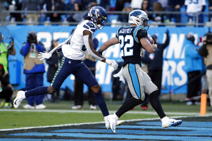 Carolina Panthers running back Christian McCaffrey (22) runs into the end zone for a touchdown as Seattle Seahawks cornerback Tre Flowers (21) chases during the second half of an NFL football game in Charlotte, N.C., Sunday, Dec. 15, 2019. (AP Photo/Brian Blanco)