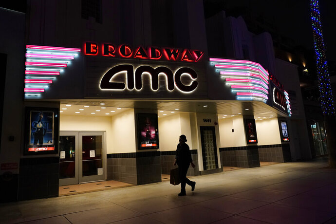 A shopper walks past a closed AMC movie theater Thursday, Nov. 19, 2020, in Santa Monica, Calif. California Gov. Gavin Newsom is imposing an overnight curfew as the most populous state tries to head off a surge in coronavirus cases. On Thursday, Newsom announced a limited stay-at-home order in 41 counties that account for nearly the entire state population of just under 40 million people. (AP Photo/Marcio Jose Sanchez)