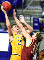 Drexel forward Mate Okros (21) shoots against Elon forward Simon Wright (33) during the first half of an NCAA college basketball game for the Colonial Athletic Association men's tournament championship in Harrisonburg, Va., Tuesday, March 9, 2021. (AP Photo/Daniel Lin)