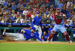 Chicago Cubs' David Bote, left, slides into home on the hit by Albert Almora Jr. as Philadelphia Phillies catcher J.T. Realmuto, right, looks to throw the ball to second during the fourth inning of a baseball game, Thursday, Aug. 15, 2019, in Philadelphia. (AP Photo/Chris Szagola)
