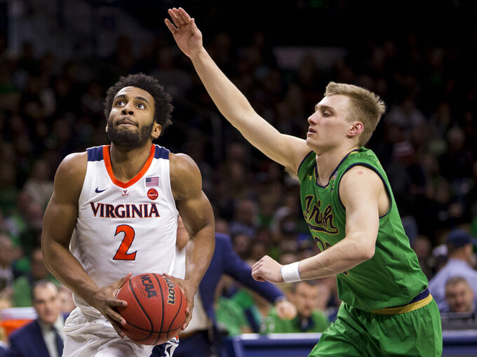 Virginia's Braxton Key (2) drives past Notre Dame's Dane Goodwin (23) during the first half of an NCAA college basketball game Saturday, Jan. 26, 2019, in South Bend, Ind. (AP Photo/Robert Franklin)