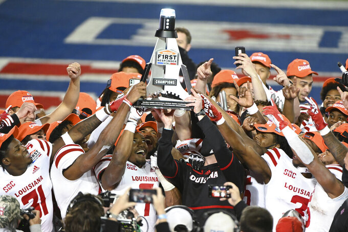 Louisiana-Lafayette linebacker Ferrod Gardner (7), coach Billy Napier and others hold up the trophy after a 31-24 win over UTSA in the First Responder Bowl NCAA college football game in Dallas, Saturday, Dec. 26, 2020. (AP Photo/Matt Strasen)
