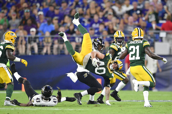 Green Bay Packers linebacker Curtis Bolton (40) is upended by Baltimore Ravens running back Justice Hill (43) after intercepting a pass from Ravens quarterback Trace McSorley, not visible, during the first half of a NFL football preseason game, Thursday, Aug. 15, 2019, in Baltimore. (AP Photo/Nick Wass)