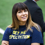 Brenda Tracy, a sexual assault survivor and activist, waits on the Michigan Stadium field for the pregame coin toss, before an NCAA college football game between Michigan and Western Michigan in Ann Arbor, Mich., Saturday, Sept. 8, 2018. Tracy accepted an offer from Michigan coach Jim Harbaugh to be an honorary captain for the season-opening game after she spoke to the team. (AP Photo/Tony Ding)