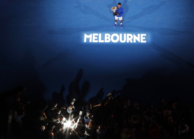 Serbia's Novak Djokovic, top, poses for photographers with his trophy after defeating Spain's Rafael Nadal in the men's singles final at the Australian Open tennis championships in Melbourne, Australia, Jan. 27, 2019. (AP Photo/Mark Schiefelbein)
