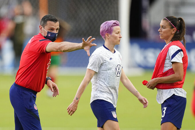 FILE - United States women's national soccer team coach Vlatko Andonovski talks with Megan Rapinoe, center, and Alex Morgan before an international friendly soccer match against Portugal in Houston, in this Thursday, June 10, 2021, file photo. In Tokyo the Americans will play for their first world championship under coach Vlatko Andonovski. His immensely deep and talented squad includes the sport's biggest names: Alex Morgan, Megan Rapinoe, Christen Press and Carli Lloyd.  (AP Photo/David J. Phillip, File)