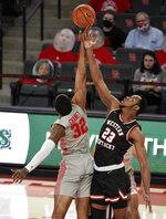 Houston forward Reggie Chaney (32) and Western Kentucky center Charles Bassey reach for the opening tip-off during the first half of an NCAA college basketball game, Thursday, Feb. 25, 2021, in Houston. (AP Photo/Eric Christian Smith)