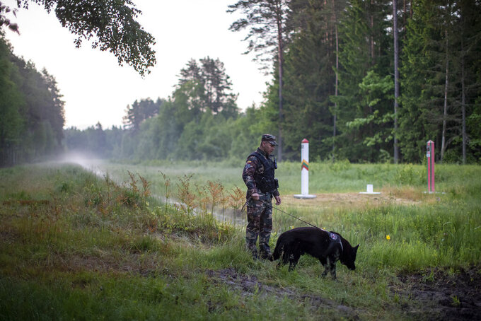 A member of the Lithuania State Border Guard Service patrols on the border with Belarus, near small town Kapciamiestis, some 160km (100 miles) of the capital Vilnius, Lithuania, Thursday, June 10, 2021. Lithuania has detained nine Iraqi asylum-seekers who had entered the Baltic country from Belarus, officials said Monday, pointing a finger at Belarus for allegedly being involved in sending repeated groups of immigrants into Lithuania. (AP Photo/Mindaugas Kulbis)