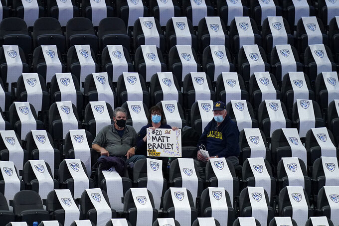 Fans, socially distanced as a precaution against coronavirus, watch during the second half of an NCAA college basketball game between Stanford and California in the first round of the Pac-12 men's tournament Wednesday, March 10, 2021, in Las Vegas. (AP Photo/John Locher)