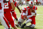Cincinnati quarterback Desmond Ridder, right, is tackled on the run by Miami of Ohio defensive back Sterling Weatherford, center, in the first half of an NCAA college football game, Saturday, Sept. 14, 2019, in Cincinnati. (AP Photo/John Minchillo)