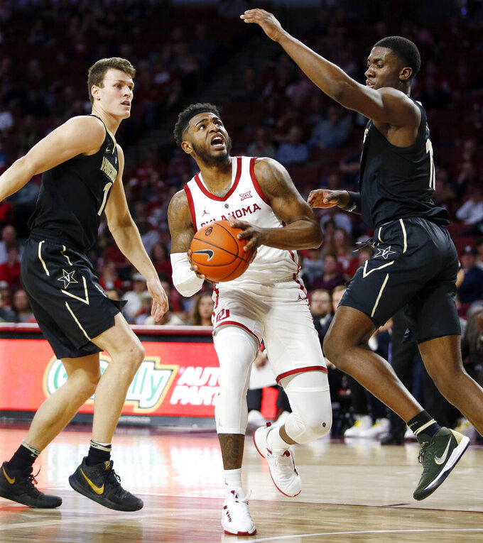 Oklahoma's Rashard Odomes (1) drives to the basket between Vanderbilt's Yanni Wetzell (1), left, and Simisola Shittu (11) during the second half of an NCAA college basketball game in Norman, Okla., Saturday, Jan. 26, 2019. (Nate Billings/The Oklahoman via AP)
