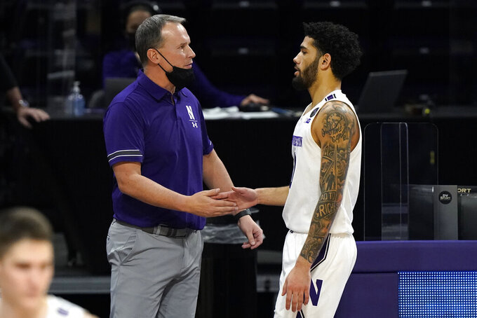 Northwestern head coach Chris Collins, left, celebrates with guard Boo Buie during the second half of an NCAA college basketball game against Michigan State in Evanston, Ill., Sunday, Dec. 20, 2020. Northwestern won 79-65. (AP Photo/Nam Y. Huh)