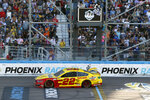 Joey Logano takes the checkered flag to win a NASCAR Cup Series auto race at Phoenix Raceway, Sunday, March 8, 2020, in Avondale, Ariz. (AP Photo/Ralph Freso)