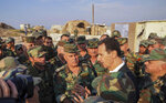 In this photo released on the official Facebook page of the Syrian Presidency, Syrian President Bashar Assad, center right, speaks with Syrian troops during his visit to the strategic town of Habeet, in the northwestern province of Idlib, Syria, Tuesday, Oct. 22, 2019. On Tuesday, Assad called the Turkish President Recep Tayyip Erdogan a