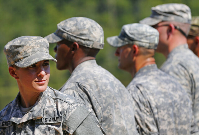 FILE - In this Aug. 21, 2015 file photo, U.S. Army Capt. Kristen Griest, left, of Orange, Conn., stands in formation during an Army Ranger School graduation ceremony at Fort Benning, Ga. In arguments to be heard on a college campus, federal appeals court judges on Tuesday, March 3, 2020, will consider whether the military's all-male draft system is constitutional. A Texas-based federal judge ruled last year that it is not, ruling in a lawsuit brought by the National Coalition for Men. The government appealed, leading to Tuesday's hearing before a three judge panel of the 5th U.S. Circuit Court of Appeals. (AP Photo/John Bazemore, File)